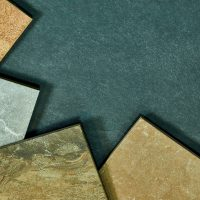 Frame of various different decorative tiles samples on stone background.
